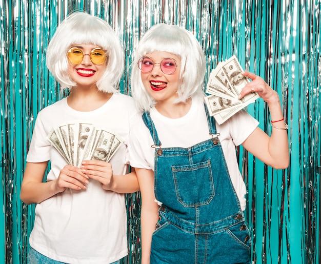 Due giovani ragazze sexy dei pantaloni a vita bassa in parrucche bianche e labbra rosse belle donne che tengono i dollari nelle mani di estate che spendono soldi Foto Gratuite