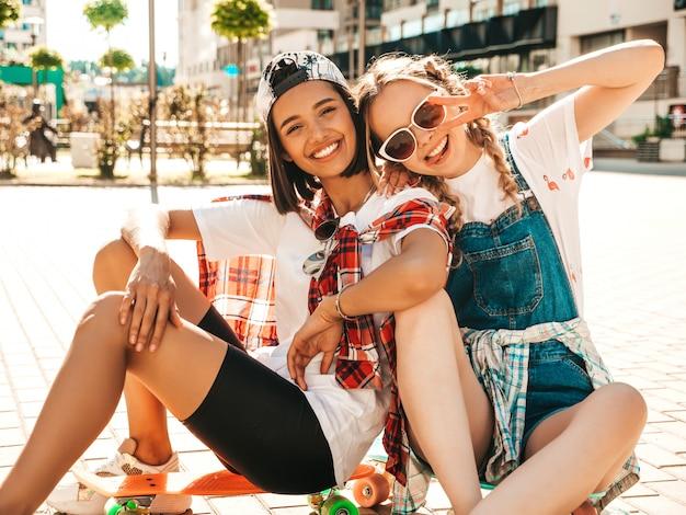 Две молодые улыбающиеся красивые девушки с красочными скейтборды пенни. женщины в летней одежде битник, сидя на улице фоне. позитивные модели веселятся и сходят с ума. показывая знак мира Бесплатные Фотографии