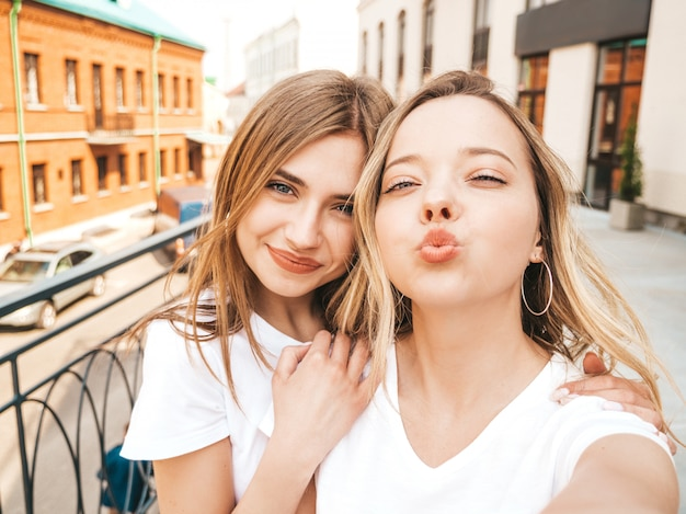 Two young smiling hipster blond women in summer white t-shirt clothes. girls taking selfie self portrait photos on smartphone.  .female making duck face Free Photo