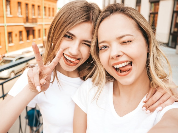 Two young smiling hipster blond women in summer white t-shirt clothes. girls taking selfie self portrait photos on smartphone.  .female shows peace sign and tongue Free Photo