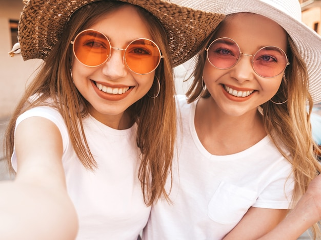 Two young smiling hipster blond women in summer white t-shirt clothes. girls taking selfie self portrait photos on smartphone. Free Photo