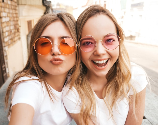 Two young smiling hipster blond women in summer white t-shirt. girls taking selfie self portrait photos on smartphone.  .female making duck face Free Photo