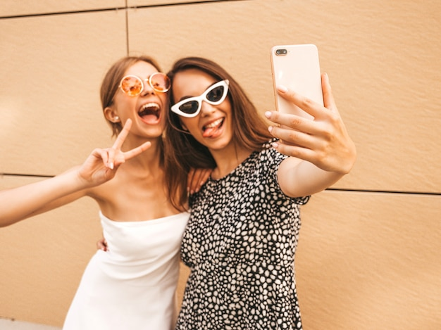 Two young smiling hipster women in summer clothes. Free Photo