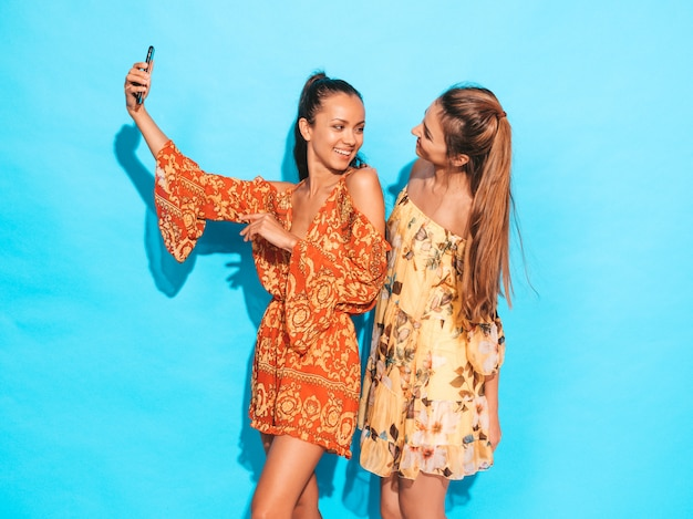 Two young smiling hipster women in summer hippie dresses.girls taking selfie self portrait photos on smartphone.models posing near blue wall in studio.female showing positive face emotions Free Photo