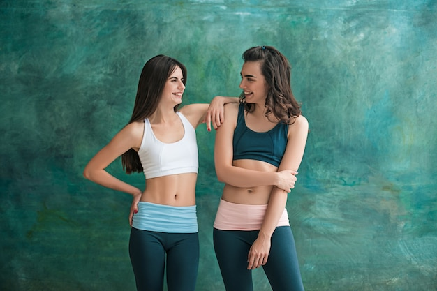 Two young sporty women posing at gym. Free Photo