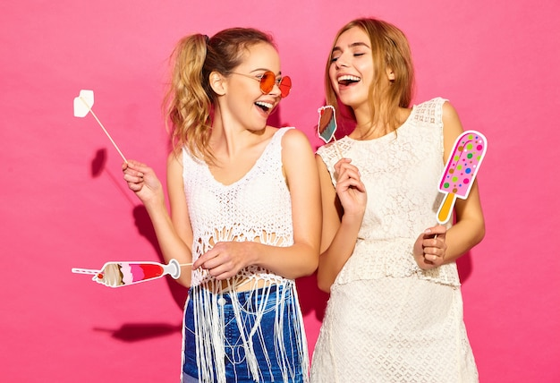 Two young stylish smiling blond women eating props sweet ice cream and fake cocktail.positive models in summer hipster clothes posing near pink wall  in sunglasses Free Photo