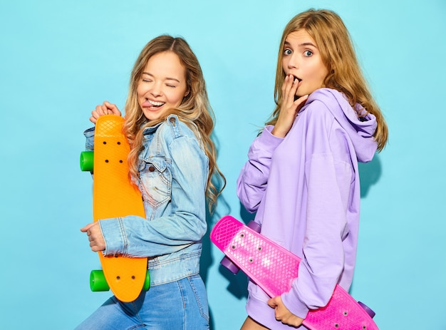 Two young stylish smiling blond women with penny skateboards. women in summer hipster sport clothes posing near blue wall . positive models Free Photo