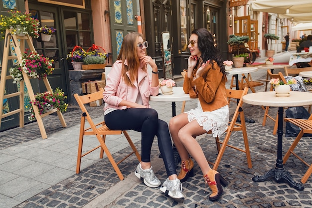 Two young stylish women sitting at cafe Free Photo