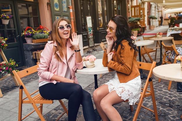 Due giovani donne alla moda che si siedono al caffè Foto Gratuite