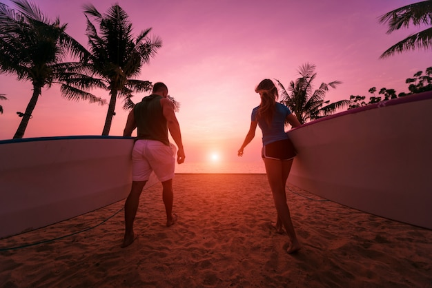 Two young surfers going into the sea with surf boards Premium Photo