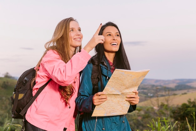 Two young traveler searching for their next destination with a map Free Photo