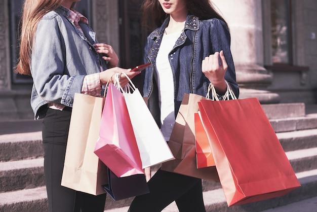 店を訪れた後、通りを歩きながら買い物袋を運ぶ2人の若い女性。 無料写真