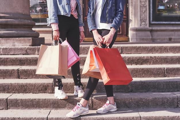 Two young woman carrying shopping bags while walking on the stairs after visiting the stores. Free Photo