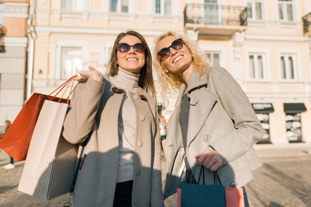 Two young women on a city street with shopping bags Premium Photo