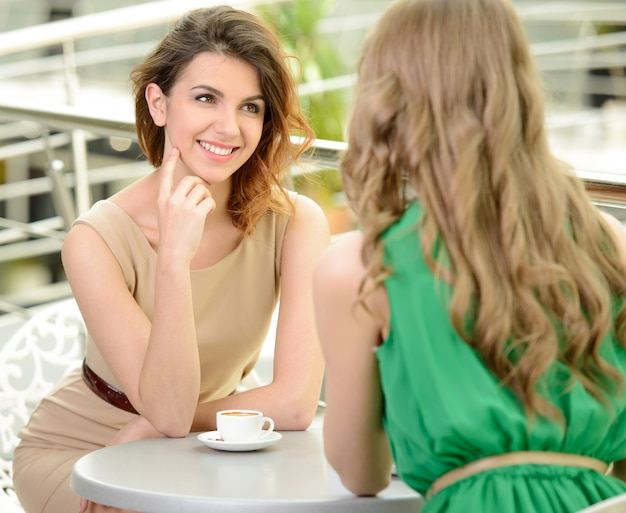 Two young women drinking coffee at the restaurant. Premium Photo