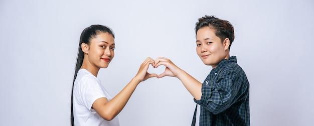2人の若い女性がお互いを愛して手マークハートをマークします。 無料写真