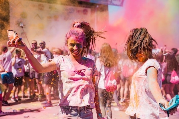 Two young women playing and enjoying with holi colors Free Photo