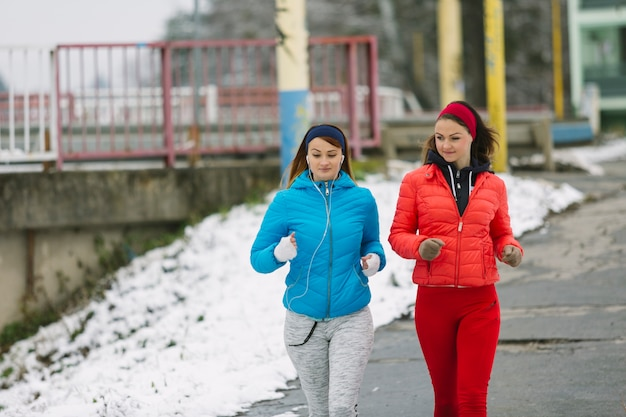 Two young women running on street in winter Free Photo