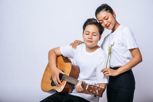2人の若い女性が椅子に座ってギターを弾きました。 無料写真