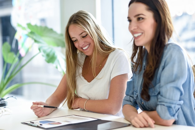 Two young women studying graphics on white desk Free Photo