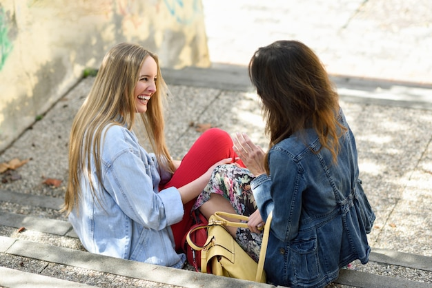 Two young women talking and laughing on urban steps. Free Photo