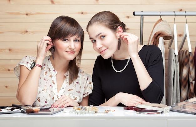 イヤリングを試着し、アクセサリーを選ぶ2人の若い女性 Premium写真