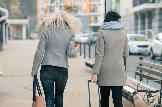 Two young women in warm clothes walking with travel suitcase Premium Photo