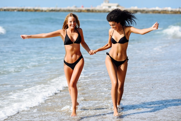 Two young women with beautiful bodies in swimwear on a tropical beach. Free Photo