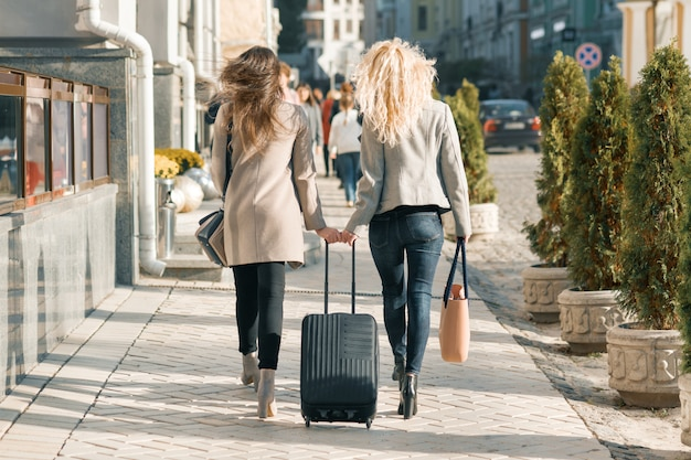 Two young women with suitcase walking along the street Premium Photo
