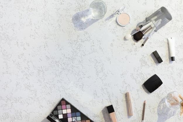 Взгляд сверху стола блоггера красоты женщины работая с компьтер-книжкой, тетрадью, декоративной косметикой, цветками, конвертом на белой twxtured пастельной таблице. плоский фон с жесткими тенями и огнями Premium Фотографии