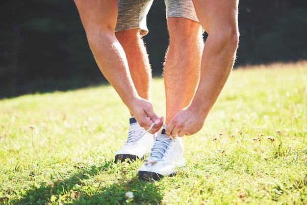 スポーツシューズを結ぶ。屋外での運動とフィットネスのトレーニングの準備をしている若いスポーツマン。 無料写真