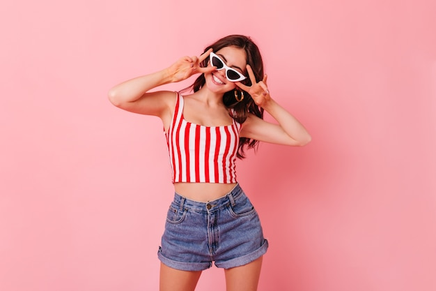 Tylish dark-haired woman in summer shorts and top smiles and shows peace sign on pink wall Free Photo