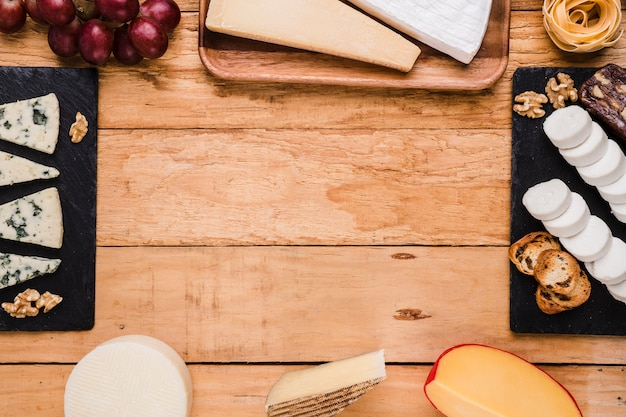 Types of cheese; grapes; walnut and pasta arranged in frame over wooden surface Free Photo