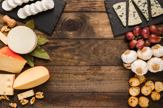 Types of cheese and ingredient on old wooden background Free Photo