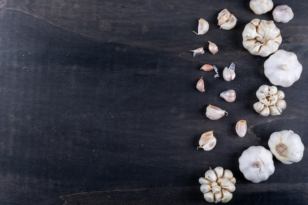 Types of garlic on right flat lay on a dark wooden table Free Photo