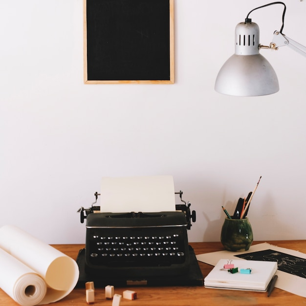 Typewriter and office supplies on table Free Photo
