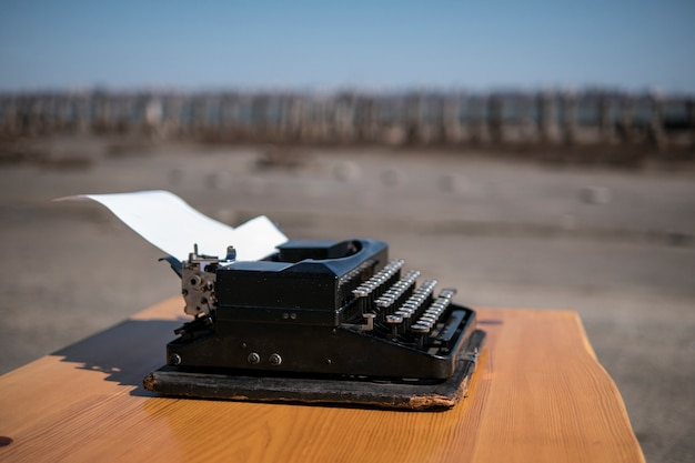 Typewriter on the table in the open air, estuary on the background Premium Photo