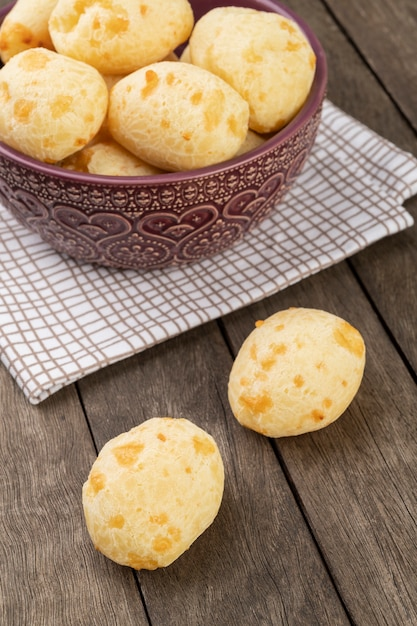 Typical brazilian cheese bun in a bowl over wooden table. Premium Photo