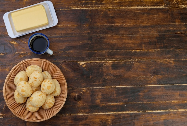 Typical brazilian cheese buns in a basket, butter and coffee with copu space Premium Photo