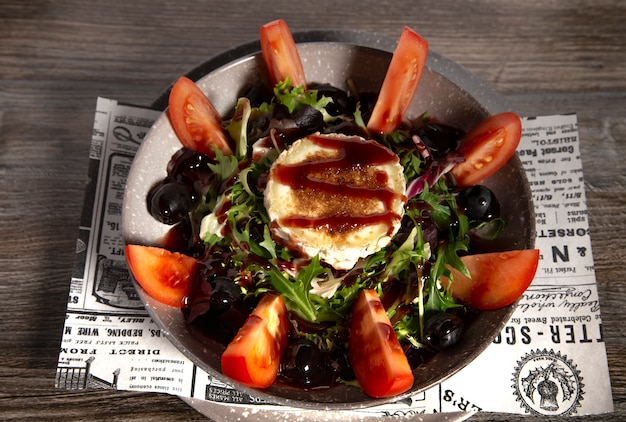 Typical spanish goat cheese salad on wooden background. isolated image Premium Photo