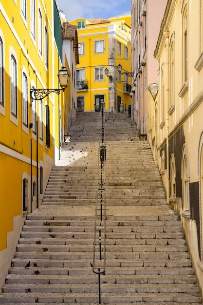ポルトガル、リスボン市の長い階段とカラフルな壁のある典型的な急な通り。 Premium写真