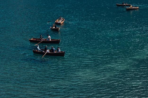 Типичные деревянные лодки с туристами на высокогорном озере. горное озеро. Premium Фотографии