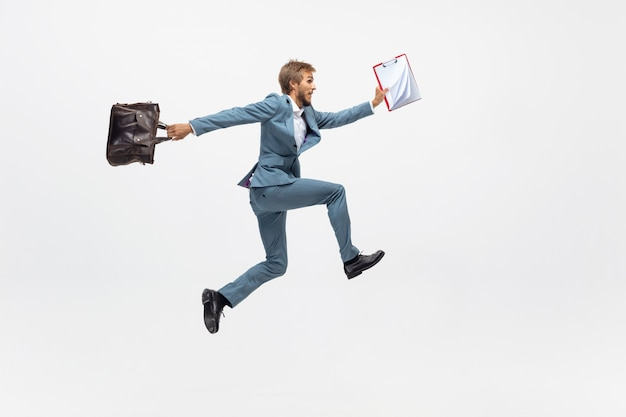 Typing. man in office clothes running, jogging on white space like professional athlete, sportsman. unusual look for businessman in motion, action with ball. sport, healthy lifestyle, creativity. Free Photo
