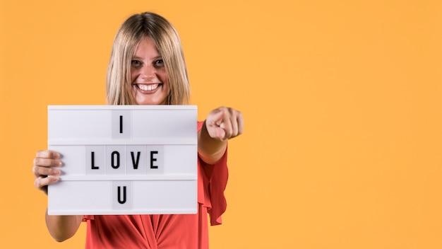 黄色の表面に対してuテキストが大好きでライトボックスを保持している女性の笑顔の正面図 無料写真