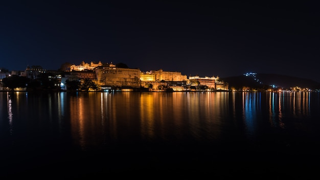 Udaipur cityscape by night. the majestic city palace reflecting lights on lake pichola, travel destination in rajasthan, india. Premium Photo