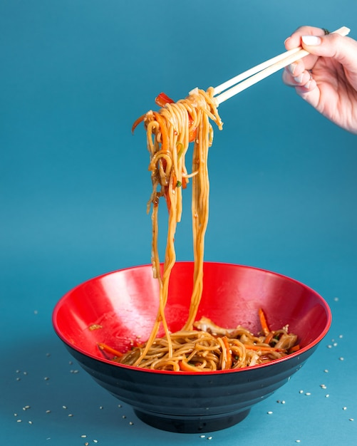 Udon stir fried noodles with bell pepper carrot spring onion soy sauce and sesame in a bowl Free Photo