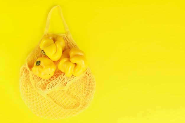 黄色のフレッシュペッパーが入った黄色のストリングバッグ。エコバイオ製品、ugい自然食品、健康、ダイエット、ベジタリアン食品 Premium写真