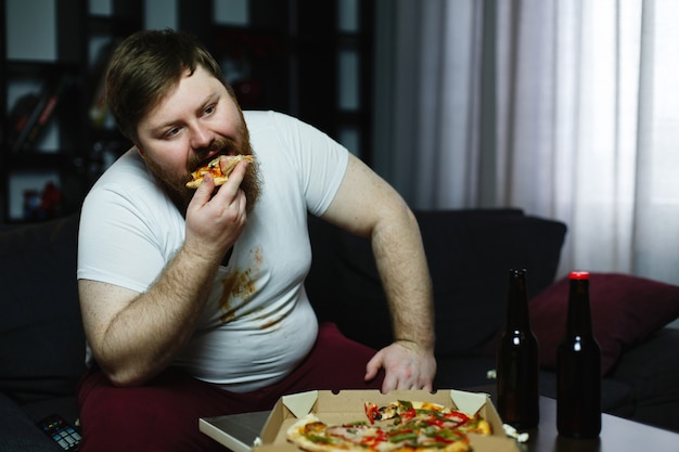 Ugly fat man eats pizza sitting on the sofa Free Photo