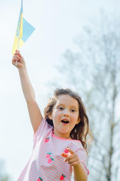 Украинский сине-желтый флаг развевается на ветру в руках маленькой украинской девочки в день независимости украины. Premium Фотографии
