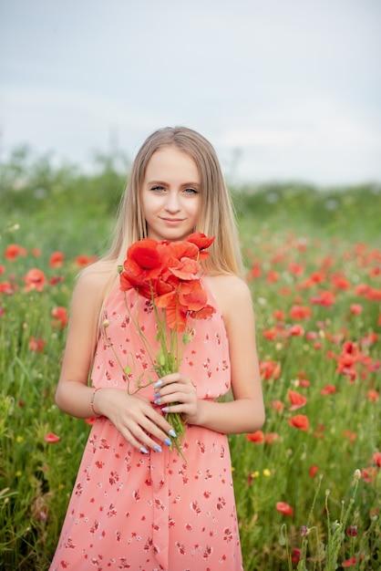 Ukrainian beautiful girl in field of poppies and wheat. Premium Photo